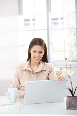 Attractive young woman browsing internet at home, using laptop, smiling. photo