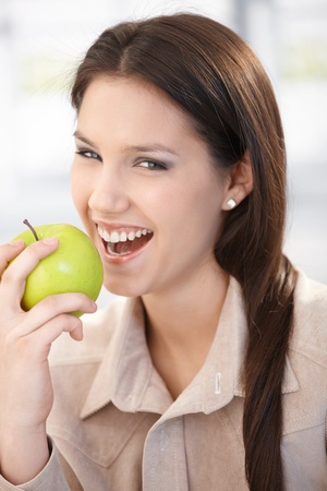 Happy young woman biting an apple, smiling. photo