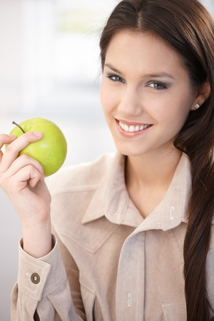 Attractive young businesswoman eating green apple, smiling. photo