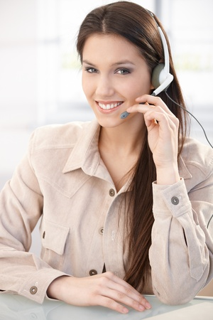 dispatcher: Portrait of pretty young dispatcher with headset, smiling.