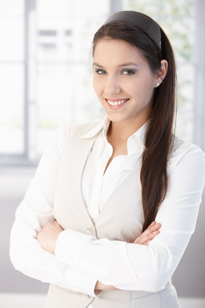 Portrait of attractive female college student smiling, standing arms crossed. photo
