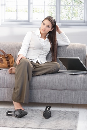 look after: Weary businesswoman sitting on sofa after work, resting. Stock Photo