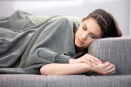 Attractive young woman laying on sofa, sleeping. photo