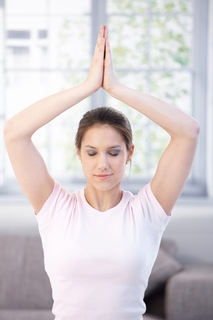 Attractive young woman meditating at home eyes closed. photo