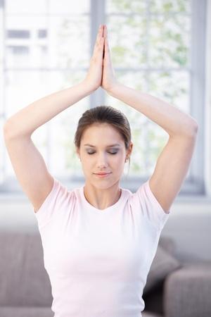 Attractive young woman meditating at home eyes closed. photo