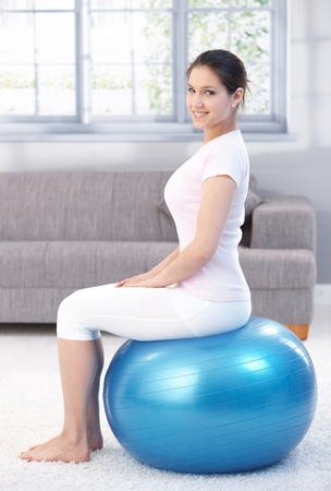 Attractive young female exercising with fit ball, smiling. photo