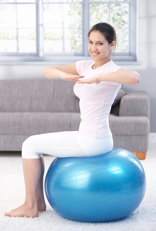 Attractive young girl exercising on fit ball at home, smiling. photo