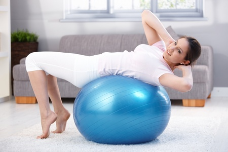 Pretty young woman laying on fit ball, doing workout, smiling. photo