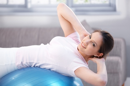 Attractive young girl exercising on fit ball, smiling. photo