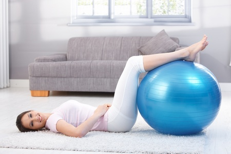 Beautiful young woman laying on floor at home, exercising on fit ball. photo