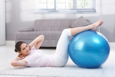 Pretty young woman doing sit-ups with fit ball, smiling.