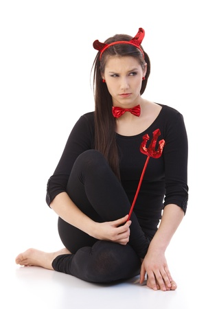 Young woman wearing devil costume, looking sad. Stock Photo - 9298966