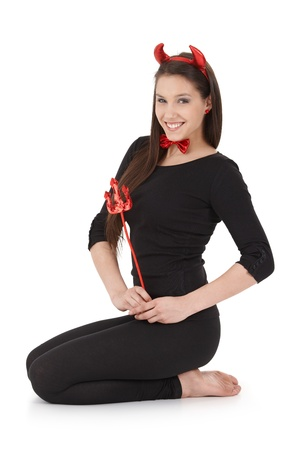 Young attractive woman kneeling on floor, wearing devil costume, smiling happily. Stock Photo - 9298960