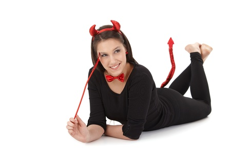 Attractive woman laying on front, dressed like black bogy, smiling. photo