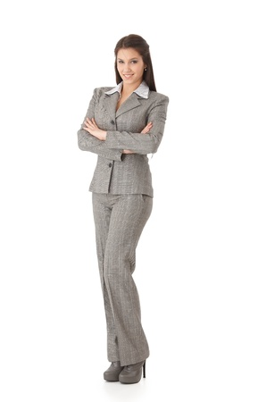 Attractive young businesswoman standing arms crossed, smiling, looking at camera. photo