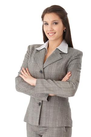 Jolie jeune femme d'affaires debout, les bras croisés, souriant, regardant la caméra.