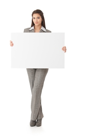 Attractive young woman standing, holding a big white panel in her hands, smiling. photo