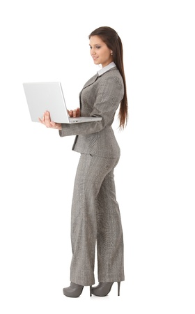 Attractive young businesswoman holding laptop in hands, working, smiling. Stock Photo - 9298968
