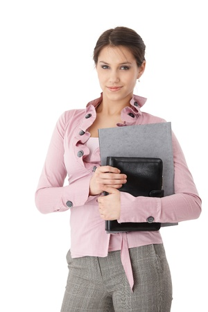 executive assistants: Pretty young secretary standing with folders in hands, smiling. Stock Photo