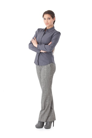 white pants: Confident young businesswoman standing arms crossed, looking at camera.