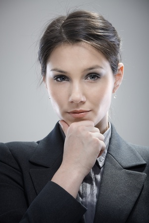 unsmiling: Portrait of attractive young businesswoman thinking.