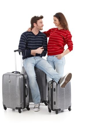 suitcases: Gelukkige jonge paar reizen met baggages, geïsoleerd op een witte achtergrond.
