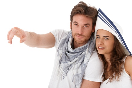 Young couple in summer outfit looking away, smiling, isolated on white background. photo