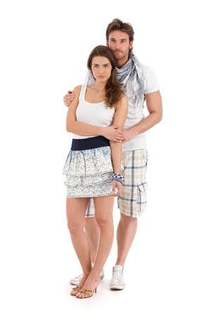 amigos abrazandose: Retrato de la feliz pareja joven abrazando ropa de verano, buscando aislado, sobre fondo blanco.