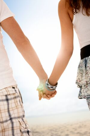 Couple walking on summer beach hand in hand, backlit by sun, focus on hands. photo