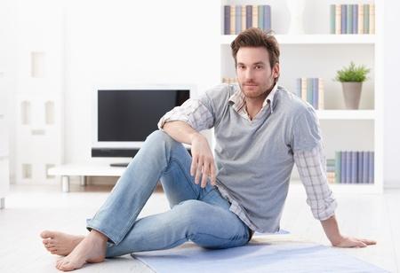 var�n: Apuesto joven sentada en el suelo en la sala de estar, sonriendo. Foto de archivo