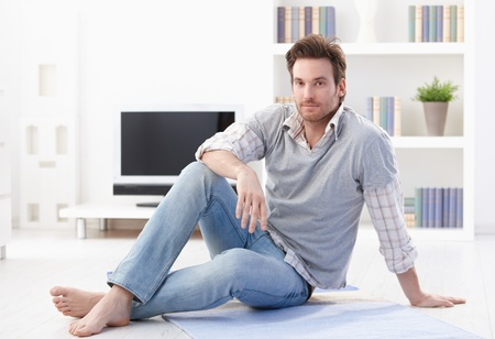 Handsome young man sitting on floor in living room, smiling. photo