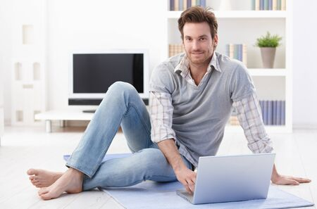 Happy young man sitting on living room floor, using laptop, smiling. photo
