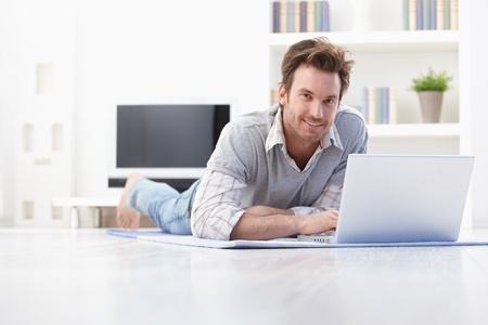 BUEN VIVIR: Apuesto joven tendido en el piso en casa, navegar por internet, sonriendo. Foto de archivo