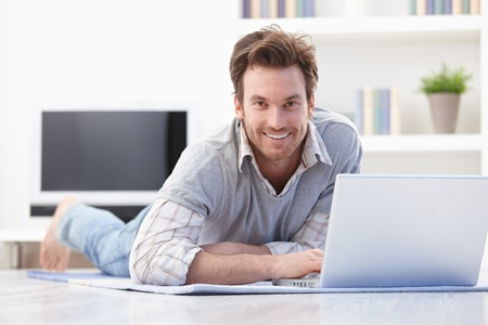 prone: Casual young man laying on floor at home, browsing internet, smiling. Stock Photo