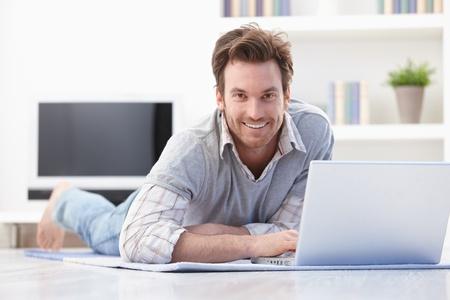 Occasionnel jeune homme pose le plancher à la maison, la navigation sur internet, souriant. Banque d'images
