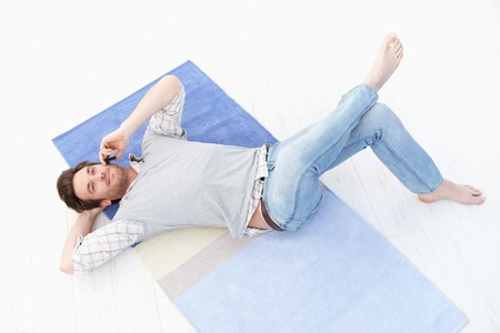Goodlooking young man laying on floor at home, talking on mobile phone, smiling. photo