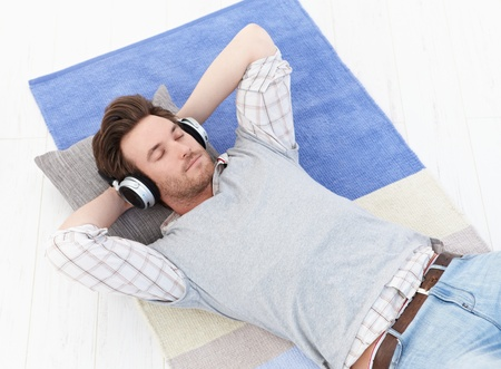 Handsome young man laying on floor, listening to music through headphones with closed eyes.