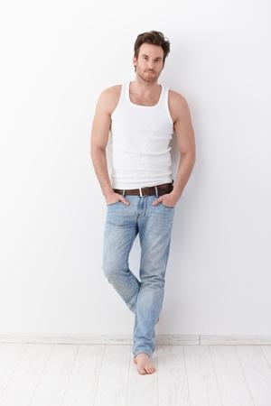 청바지와 땀 받이 입고 벽에 서, 체육 젊은 남자.