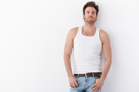 undershirt: Sexy young man standing by wall in undershirt, smiling.