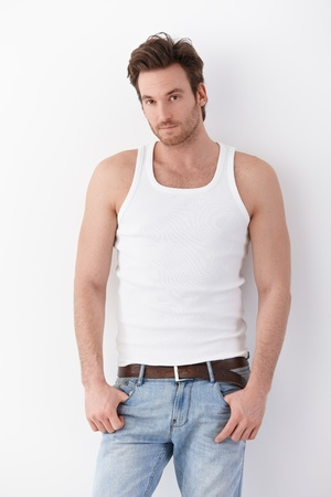 white singlet: Goodlooking young man wearing undershirt and jeans, standing by wall.