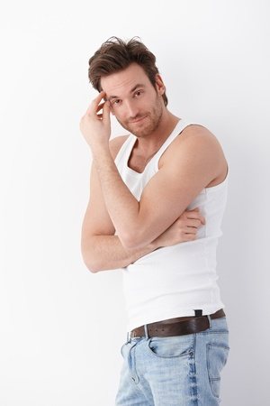 canottiera: Sexy young man wearing undershirt and jeans, posing at white wall, smiling.
