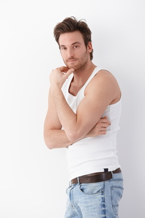 undershirt: Athletic young man standing at wall, wearing undershirt and jeans. Stock Photo