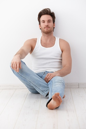 Handsome young man sitting on floor, leaning to wall, wearing undershirt and jeans. photo