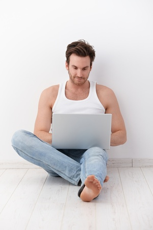Handsome young man sitting on floor at home, using laptop, smiling. photo
