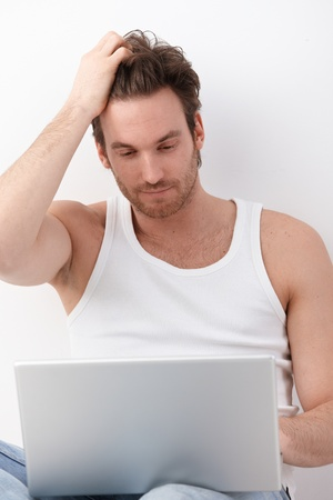 Athletic young man using laptop, browsing internet. photo