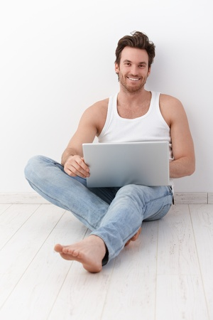 white singlet: Happy young man sitting on floor at home, using laptop, smiling. Stock Photo