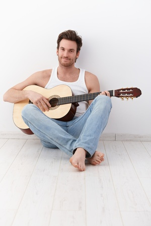 young unshaven: Sexy guitarist sitting on floor with guitar, smiling. Stock Photo