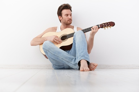 1 man only: Handsome young man playing guitar, sitting on floor.