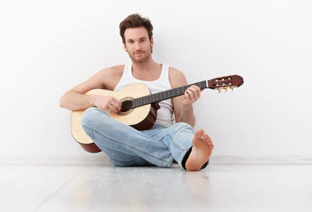 Handsome guitar player sitting on floor, practicing. photo