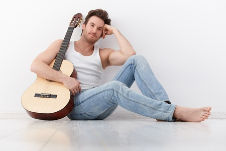 Goodlooking young man sitting by wall, holding guitar, smiling. photo